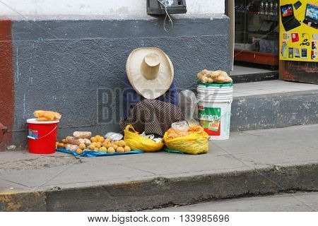 Cajamarca Peru - June 11 2016: Sleeping Andean woman sells fruit on street in Cajamarca Peru on June 11 2016