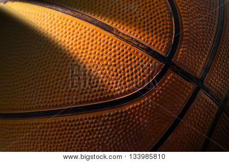 Macro photo of an old black and orange basketball with dark shadows