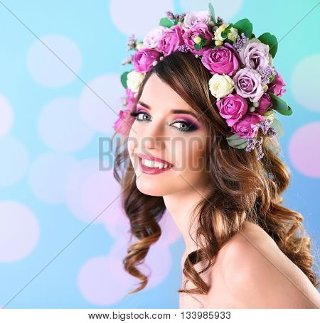 Beautiful young woman wearing floral headband on a blue festive background