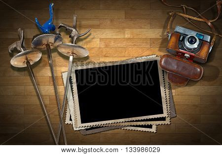 Old camera and empty old photo frames on a wooden floor (parquet) with three fencing foils