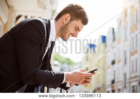 Modern vision. Positive delighted handsome man holding cell phone and leaning on the handrail while expressing joy