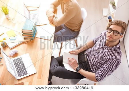I making most of my education. Top view of guy sitting with notebook, using laptop and studing with friend in background