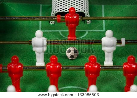 Macro photo of a mini table football game with an old black and white soccer ball