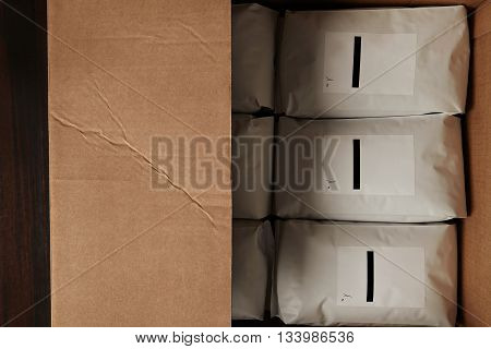 Top View Big Carton Box Full Of Blank Hermetic White Packages With Coffee Or Tea. Everything On Red