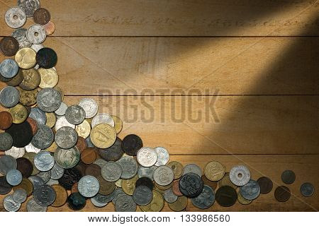 Old and vintage metallic coins on a wooden background with copy space