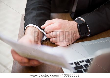 Ready to work. Pleasant man sitting at the table and holding papers while being involved in work