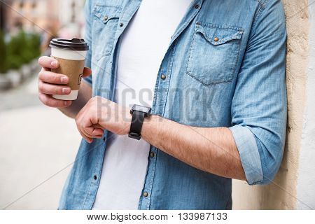 Trace time. Positive pleasant man drinking coffee and looking at his smart watch while standing in the street