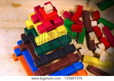 Close up of a pyramid made with colorful pieces of wood. Toy for learn the creativity and dexterity