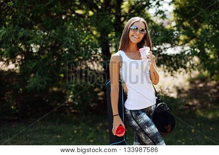 Woman drinking at the outdoor water before working out . Girl close-up, drink water