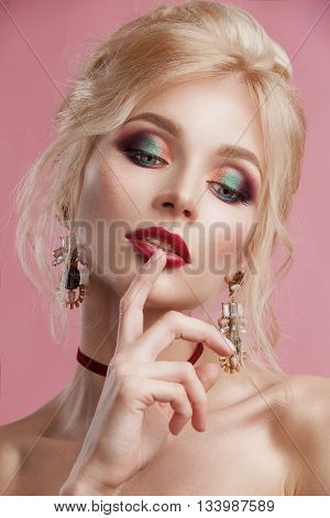Beauty woman with beautiful make-up color . Blond hair raised hair jewelry on his neck clean skin beautiful face . Portrait shot in studio on a pink background .