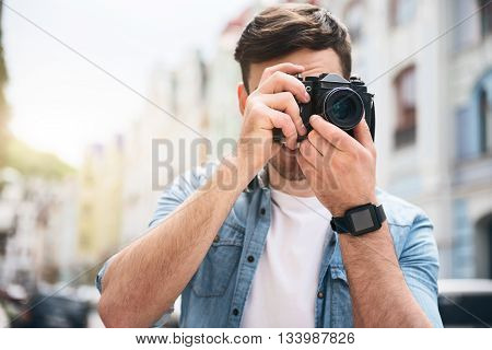Amateur photographer. Pleasant cheerful handsome man holding photo camera and making photos while resting outdoor