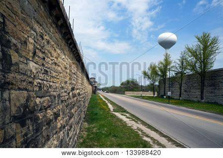 An exterior limestone wall of the old Illinois State Prison (aka Joliet Correctional Center, now abandoned) along Collins Street in Joliet, Illinois