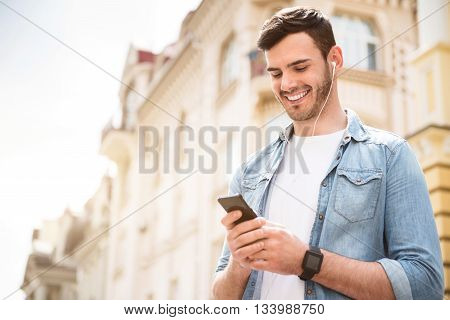 Happy time. Overjoyed handsome smiling man holding cell phone and listening to music while having a walk