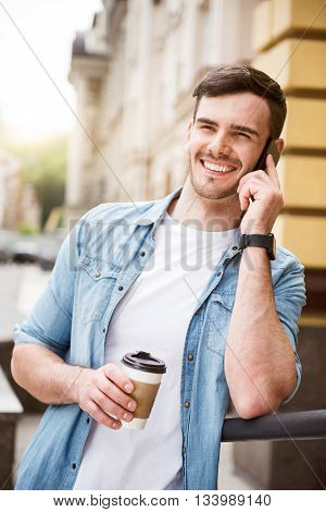 Start day positively. Cheerful handsome smiling man talking on cell phone and holding coffee while leaning on the handrail