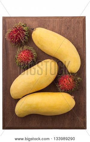 Fruits series : Yellow mango and rambutans on wooden board