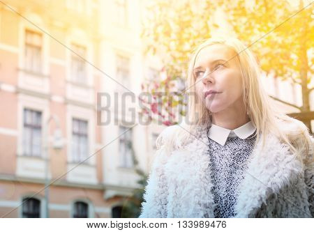 blond woman standing in the street and looking thoughtful