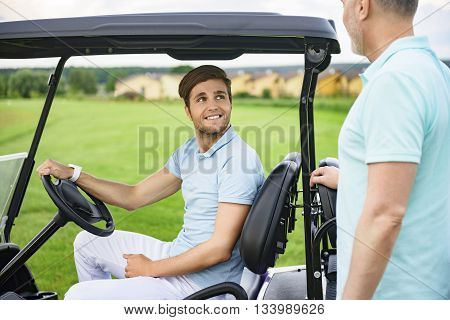 Discussing handicaps. Smiling son talking with his father on their way to tee-off, driving golf cart