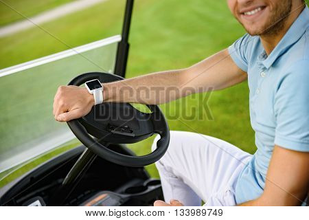 Waiting for his tee-off. Close up of young smiling guy sitting and driving golf car