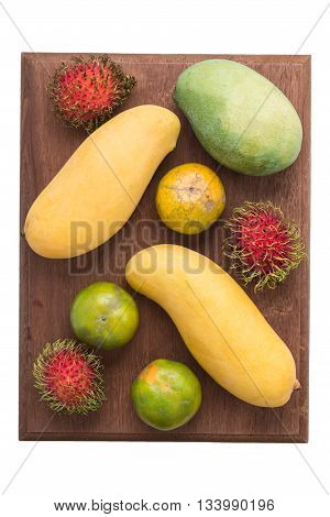 Fruits series : Yellow and green mangoes, orange and green oranges and rambutans on wooden board