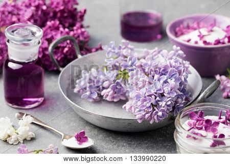 Lilac flowers sugar and syrup essential oil with flower blossoms in glass jar Grey stone background.