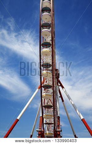 Ferris wheel and blue sky with clouds. Wide angle view.