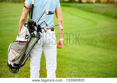 Waiting for his turn to play. Close up of golf player in blue shirt with bag of golf clubs on his back, standing on beautiful golf course