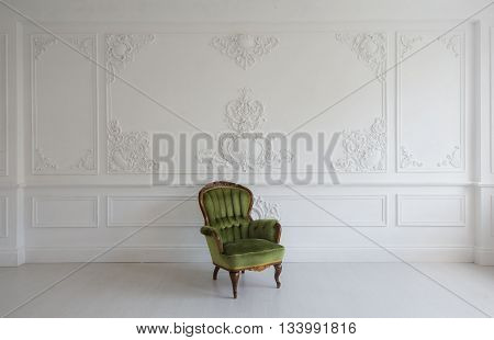 vintage luxury armchair in white room over wall design bas-relief stucco mouldings roccoco elements.