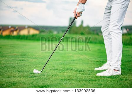 Driving it to green. Close up of golf player holding driver about to hit golf ball resting on golf course