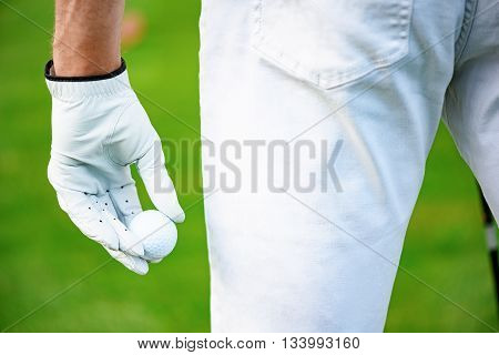 Another sucsessful golfing day. Close up of hand holding golf ball on hand, standing on course
