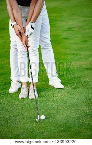 It easy to do. Close up of man assisting his girlfriend on miniature golf course, holding driver near to hit golf ball resting on field