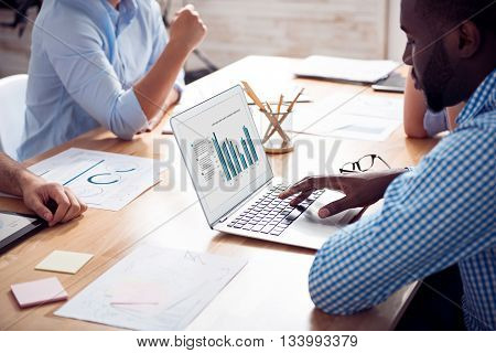 Involved in work. Positive delighted man sitting at the table and using laptop while working with his colleagues