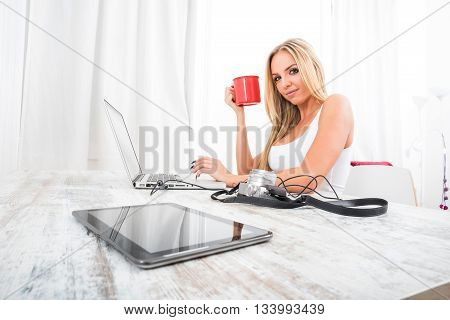 A beautiful young blond woman siting at the table having a coffee and using a laptop.