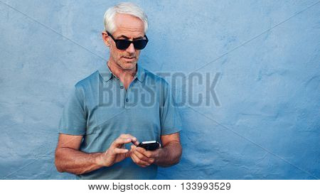 Portrait of mature man in sunglasses reading text message on her mobile phone against blue background. Middle aged caucasian male standing against blue wall with copy space.