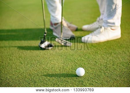 Pause in game. Close up of white golf ball lying on course with couple standing on background, holding drivers
