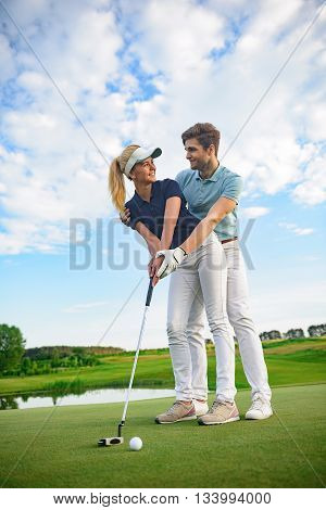 Spending day on green. Smiling young couple playing golf, holding driver and looking each other
