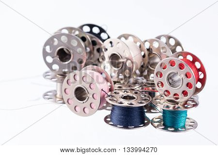Metal thread bobbins isolated on white background