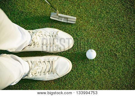 One shot to success. Top view of golfer staying near white ball, holding driver