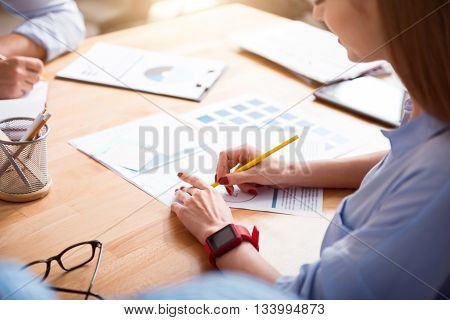 Real workaholic. Cheerful beautiful woman sitting at the table and making notes while working with her colleague