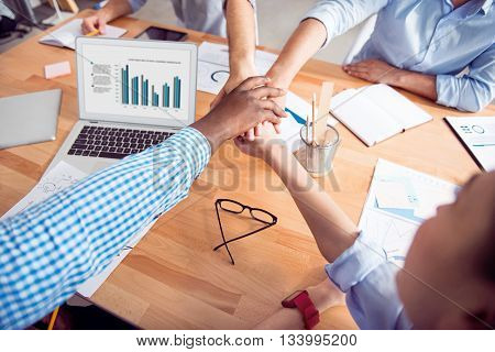 We are the one. Pleasant friendly colleagues sitting at the table and holding hands together while being involved in work