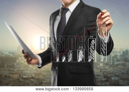 Financial growth concept with businessman holding document and drawing abstract business chart on city at sunset background
