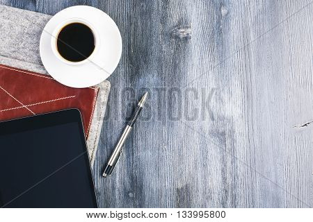 Top view of wooden desktop with blank tablet coffee cup pen and cover. Mock up