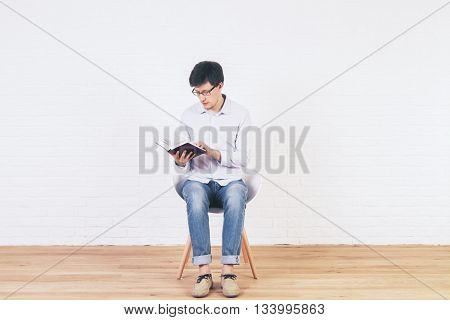 Caucasian male reading book in empty interior with brick wall and wooden floor