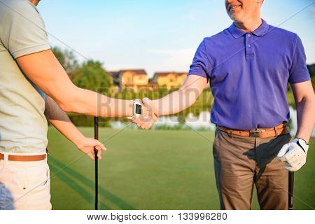 Close up of golfing partners shaking hands after great game, standing on golf course