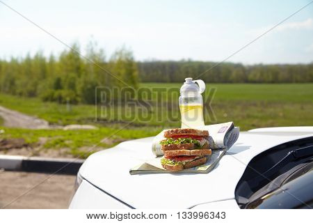 Road trip breakfast on a car hood - sandwiches and lemonade