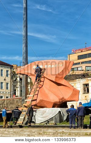 Kursk, Russia - October 1, 2015: A team of workers restoring memorial sign Fighters for the Soviet regime, Established in 1967