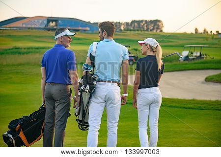 We getting ready to play golf. Smiling golfing companions standing on golf course, discussing game, holding golf bags with golf cart on background