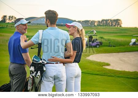 Attractive golfers. Smiling golfing companions standing on golf course and looking each other with golf cart on background