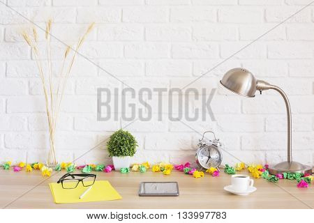 Creative desktop with crumpled paper tablet coffee cup lamp wheat spikes and other items on white brick wall background