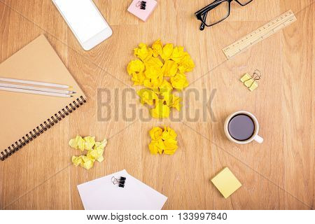 Top view of wooden desktop with crumpled paper lightbulb coffee white smartphone and various stationery items. Idea concept
