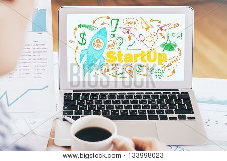 Start up concept with businessman drinking coffe and looking at laptop screen with rocket ship sketch